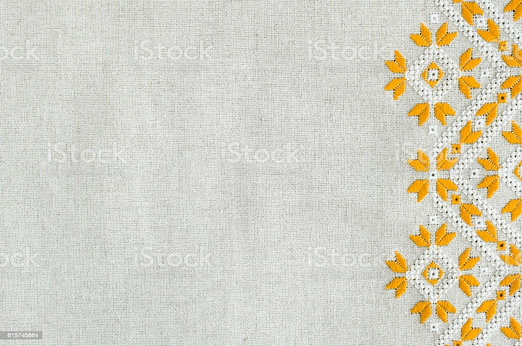 Embroidered fragment on flax by yellow and white cotton threads. stock photo