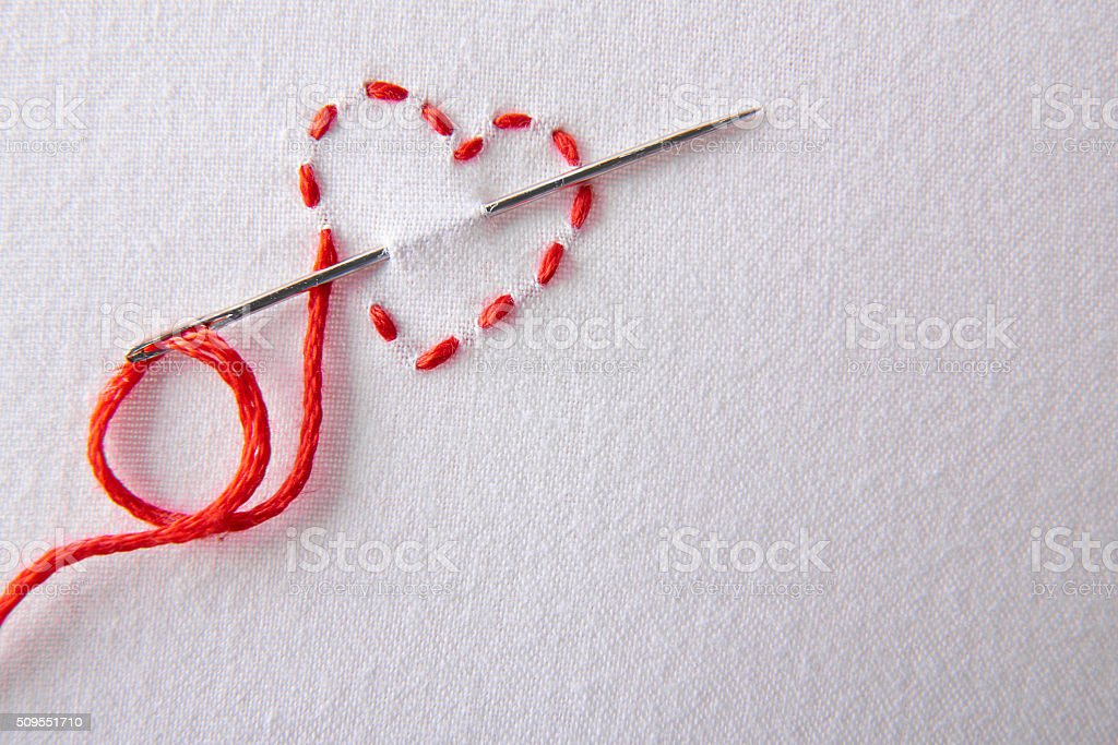 Embroidered red heart on a white cloth close up stock photo