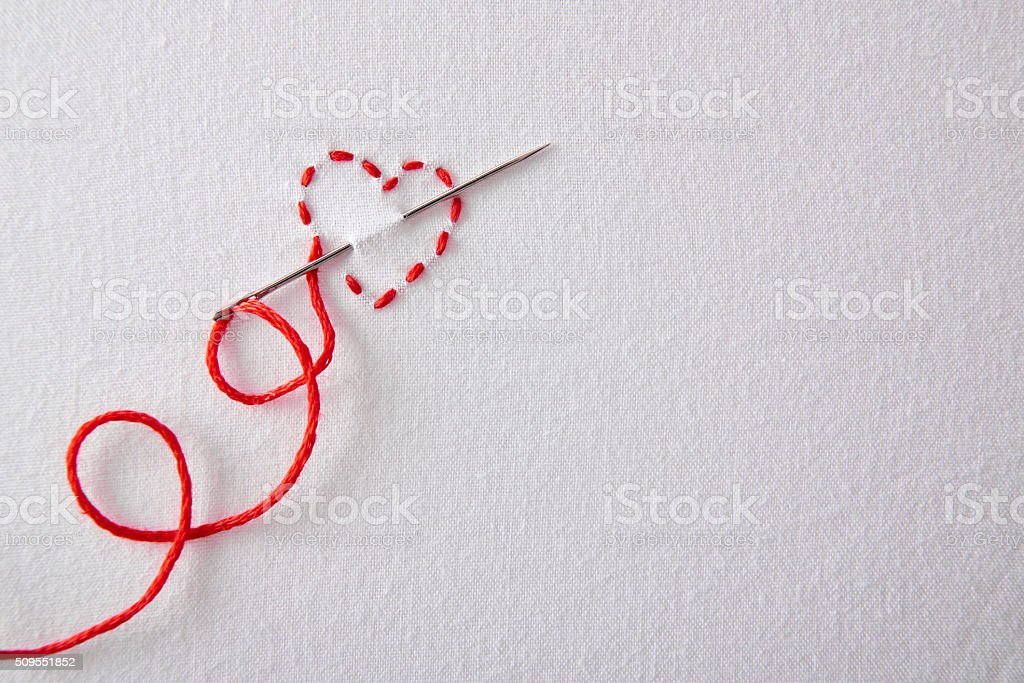 Embroidered red heart on a white cloth top view stock photo