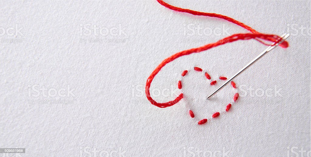 Embroidered red heart on a white cloth with needle punctured stock photo