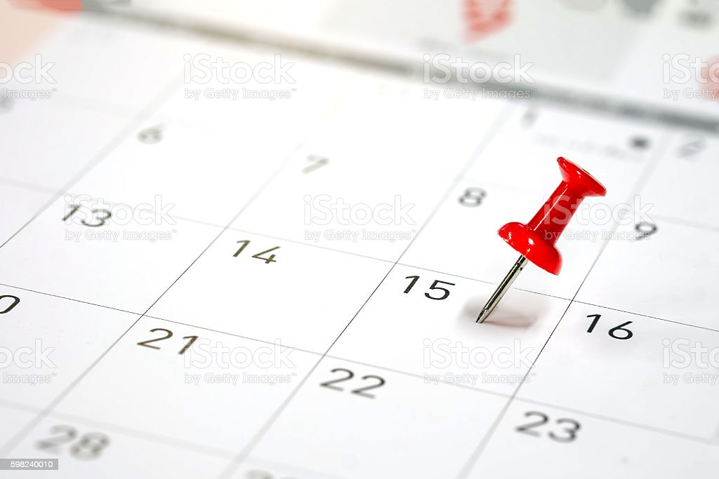 Embroidered red pins on a calendar stock photo