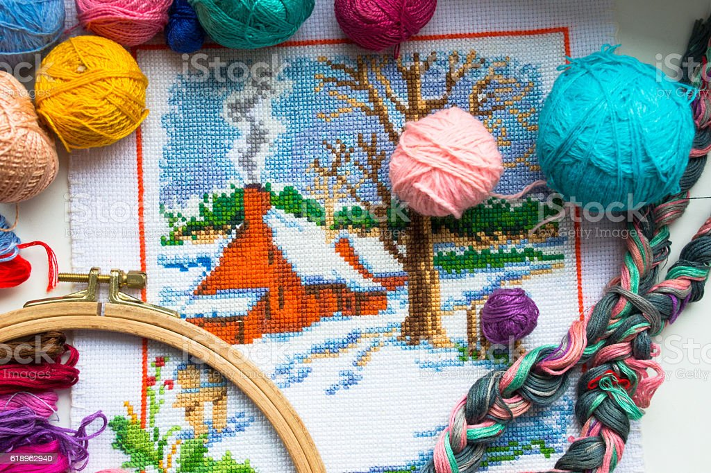 Embroidered winter house with yarn for colour knitting and tambour stock photo