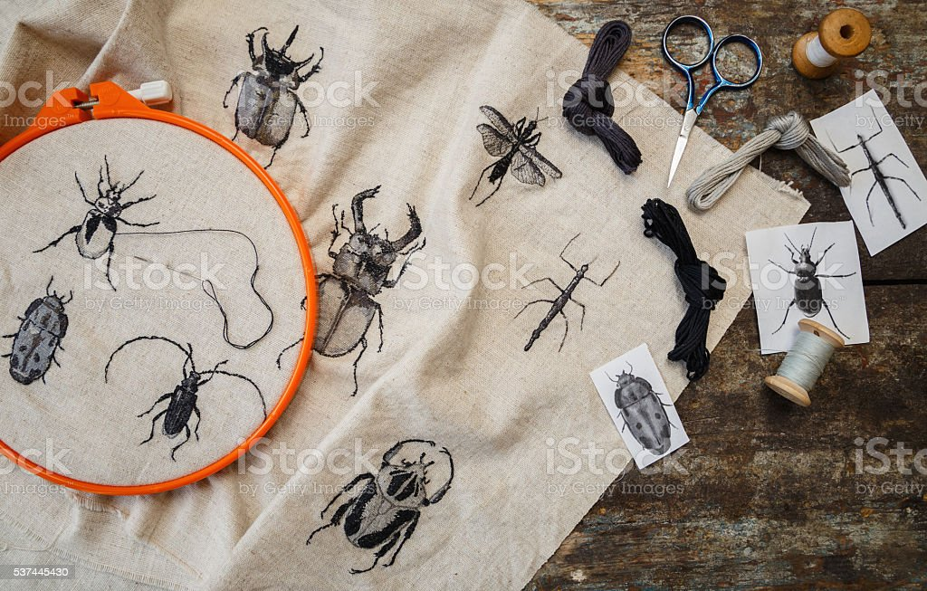 Embroidery in process with hoop and sewing threads on table. stock photo