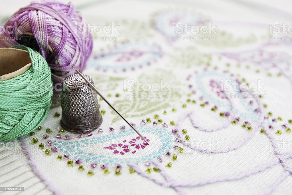 Embroidery thread, needle and thimble on a embroidery. stock photo