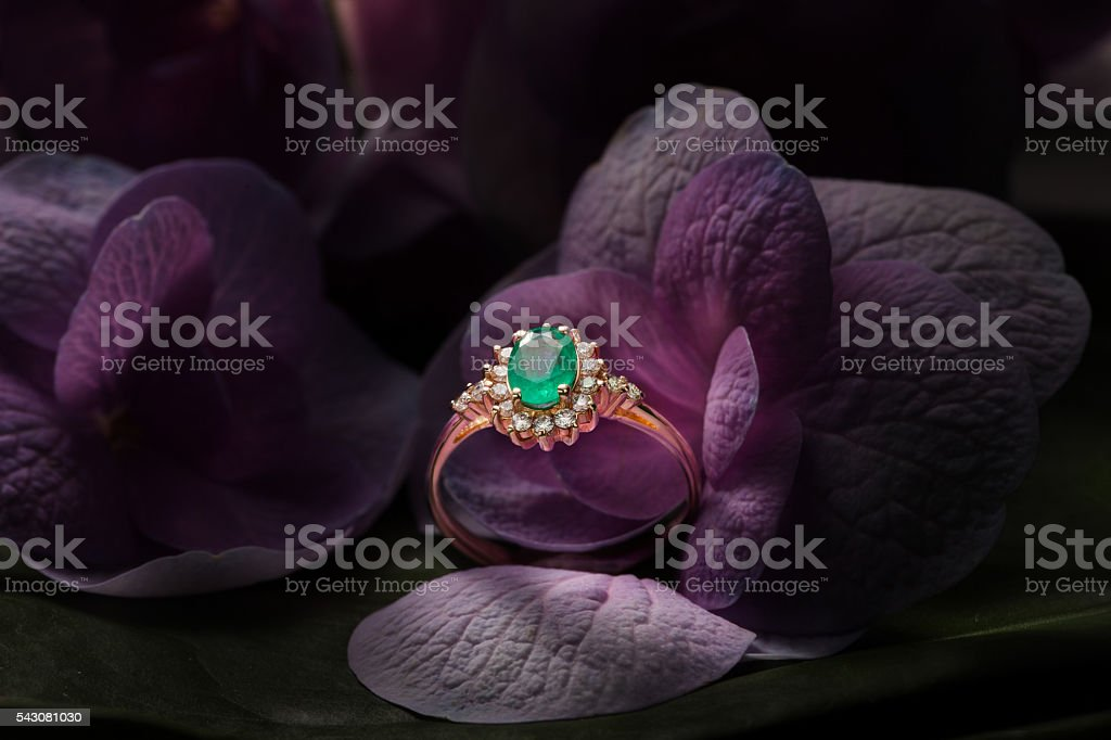 Emerald gold ring with diamonds closeup on a flower bokeh stock photo
