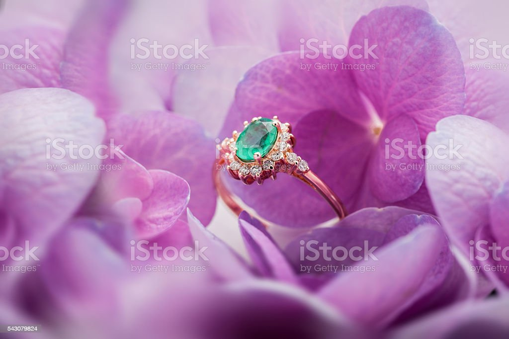 Emerald gold ring with diamonds closeup on floral bokeh stock photo