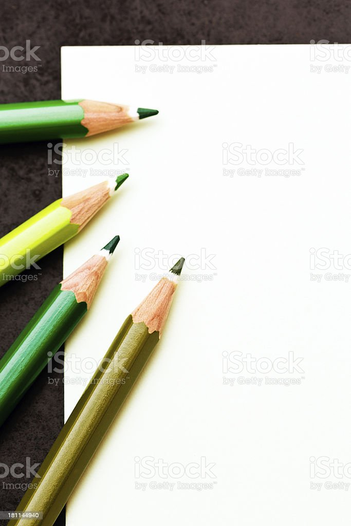 Emerald, olive and lime green crayons on blank sketchpad royalty-free stock photo