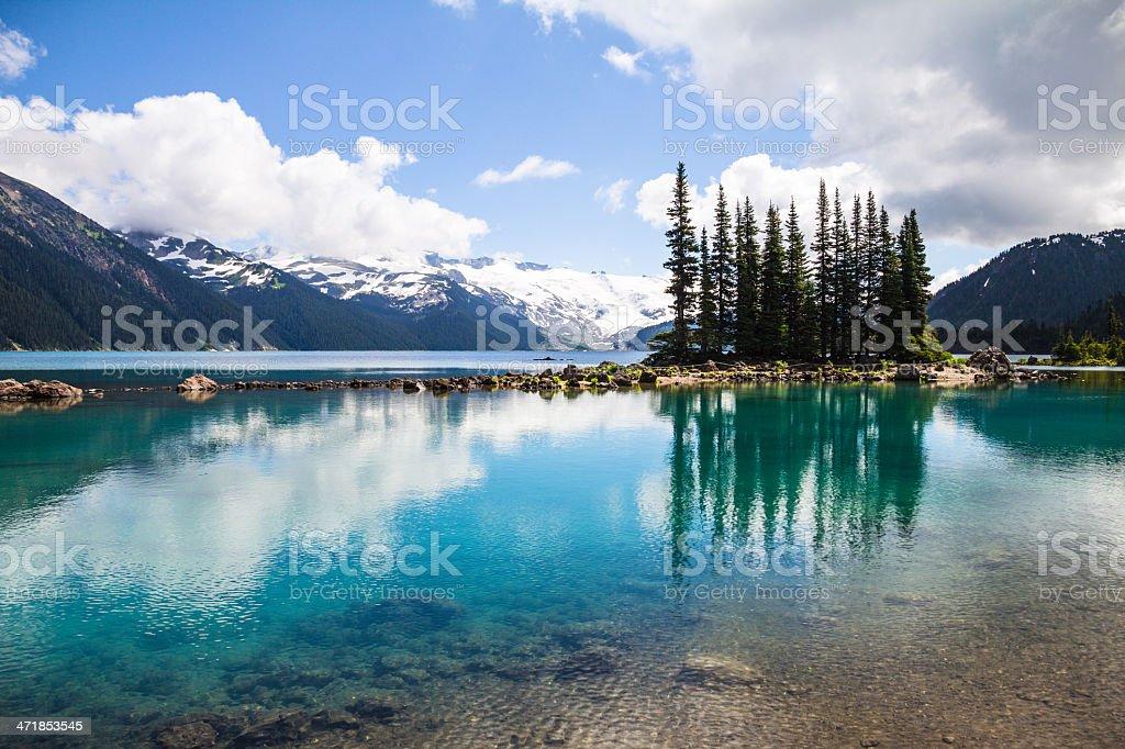 Emerald waters of Garibaldi Lake reflect bottle-green tree silhouettes stock photo