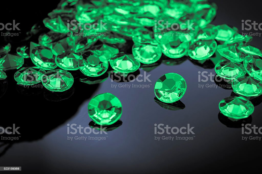 Emeralds scattered on a shiny surface stock photo