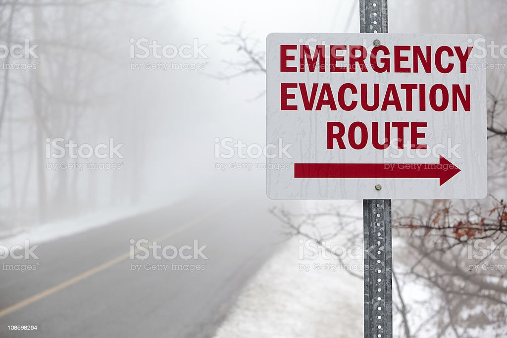 'Emergency evacuation route' sign on the mist road stock photo