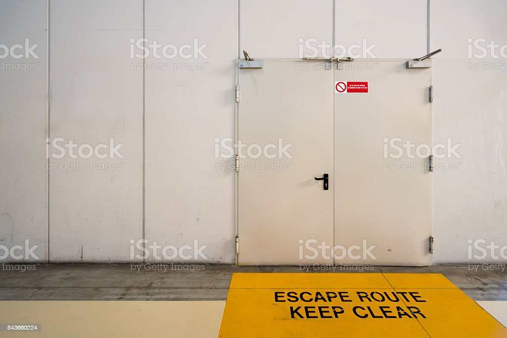 Emergency exit door with keep clear warning message on floor stock photo