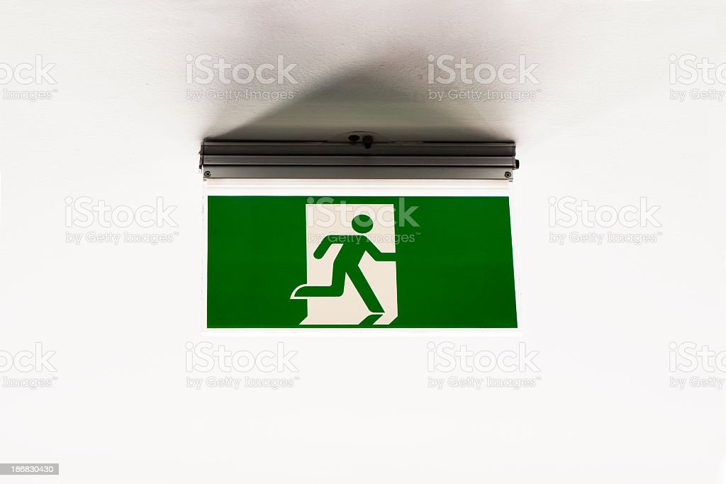 Emergency exit sign against white ceiling, copy space royalty-free stock photo