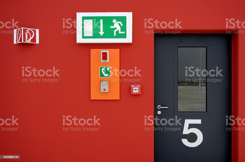 Emergency exit sign and fire alarm button and black door stock photo