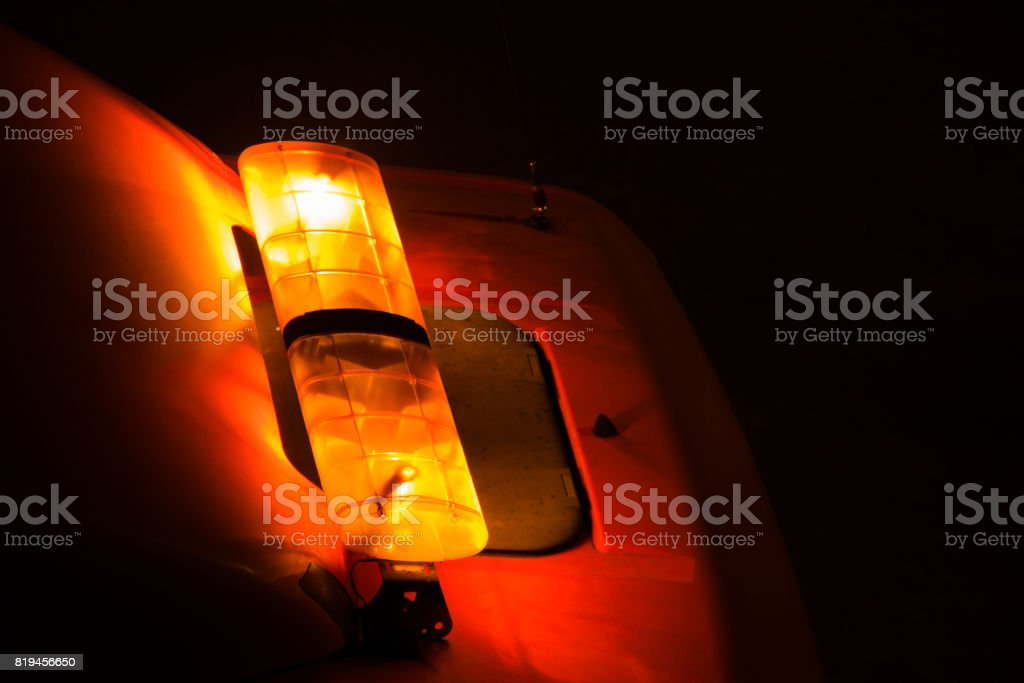 Emergency light or Flashing beacon. Orange flashing and revolving light on top of a support and services vehicle. stock photo