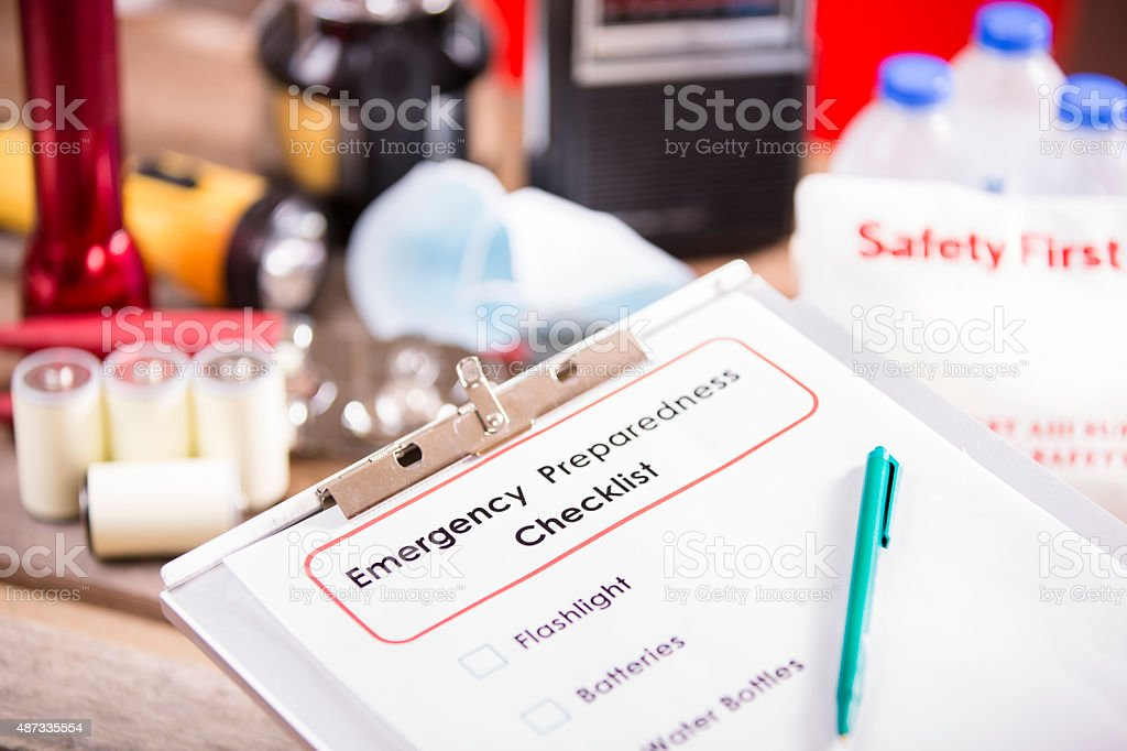 Emergency preparedness checklist and pile of supplies to be used in...