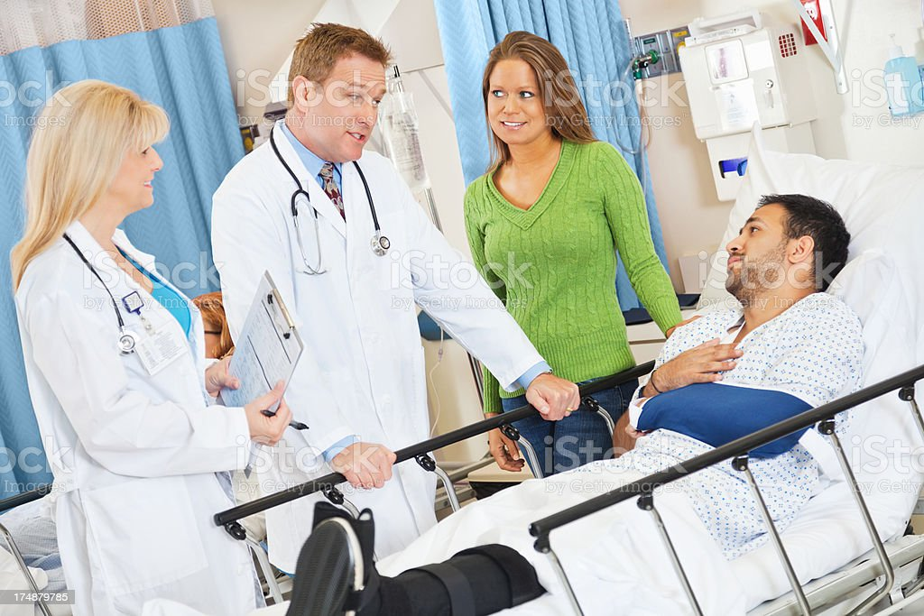Emergency room doctors checking on injured patient in hospital stock photo