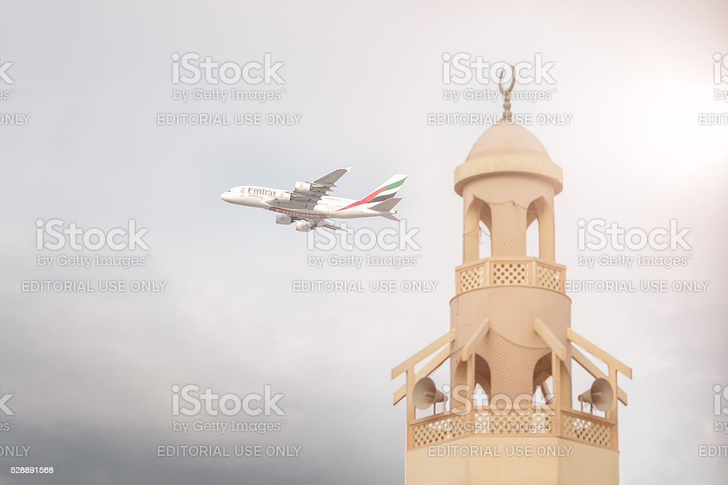 Emirates aircraft is taking off from DXB airport near mosque stock photo