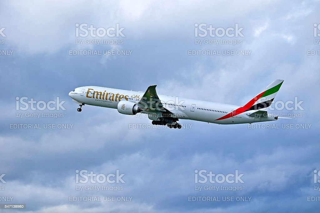 Emirates Airline Boeing 777 aircraft is flying in the sky stock photo