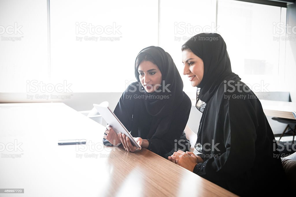 Emirati Arab businesswomen using digital tablet stock photo