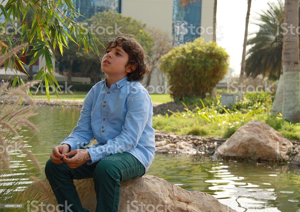 Emirati boy sat next to pond in park. stock photo