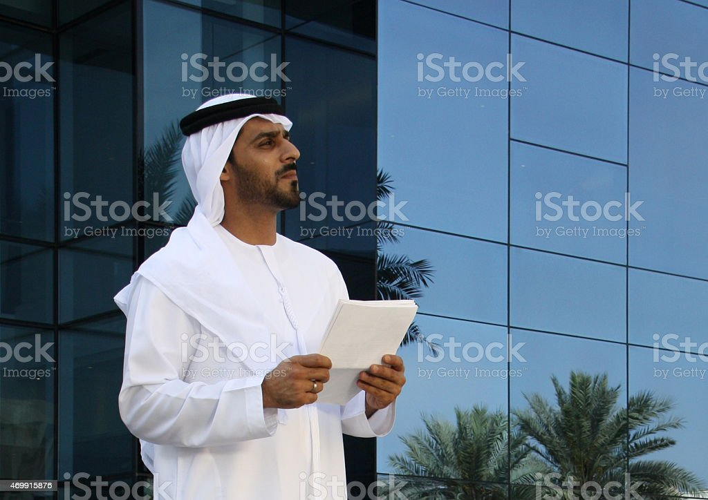 Emirati business man in traditional dress holding documents, Dubai UAE stock photo