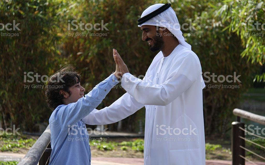 Emirati father in traditional dress and son high-five, Dubai, UAE stock photo
