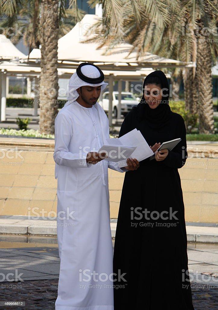 Emirati man and woman having a discussion, Dubai, UAE stock photo