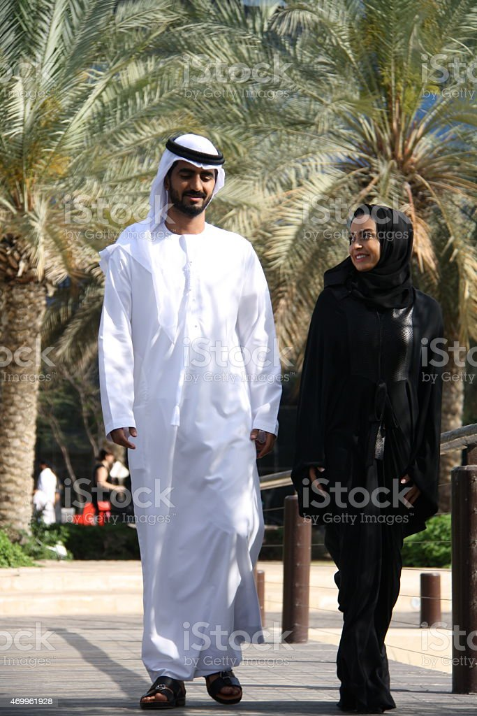 Emirati man and woman walking in park. stock photo