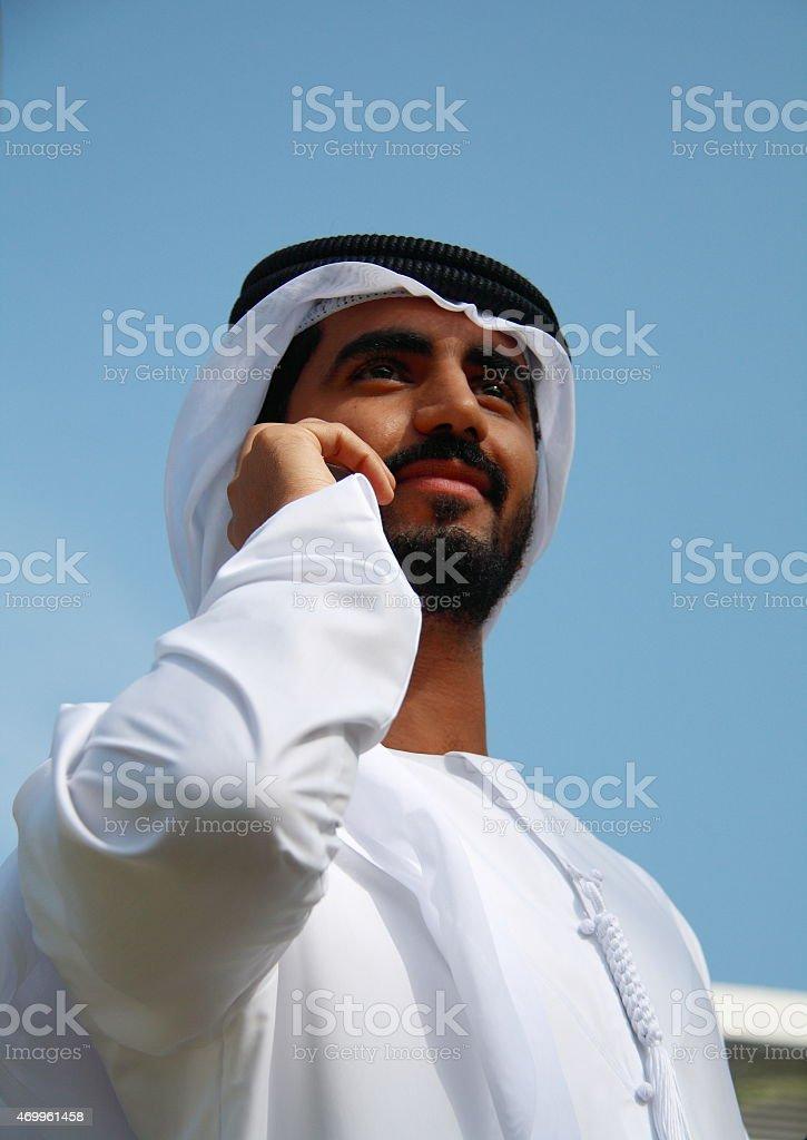Emirati man in traditional dress on mobile phone, Dubai, UAE stock photo