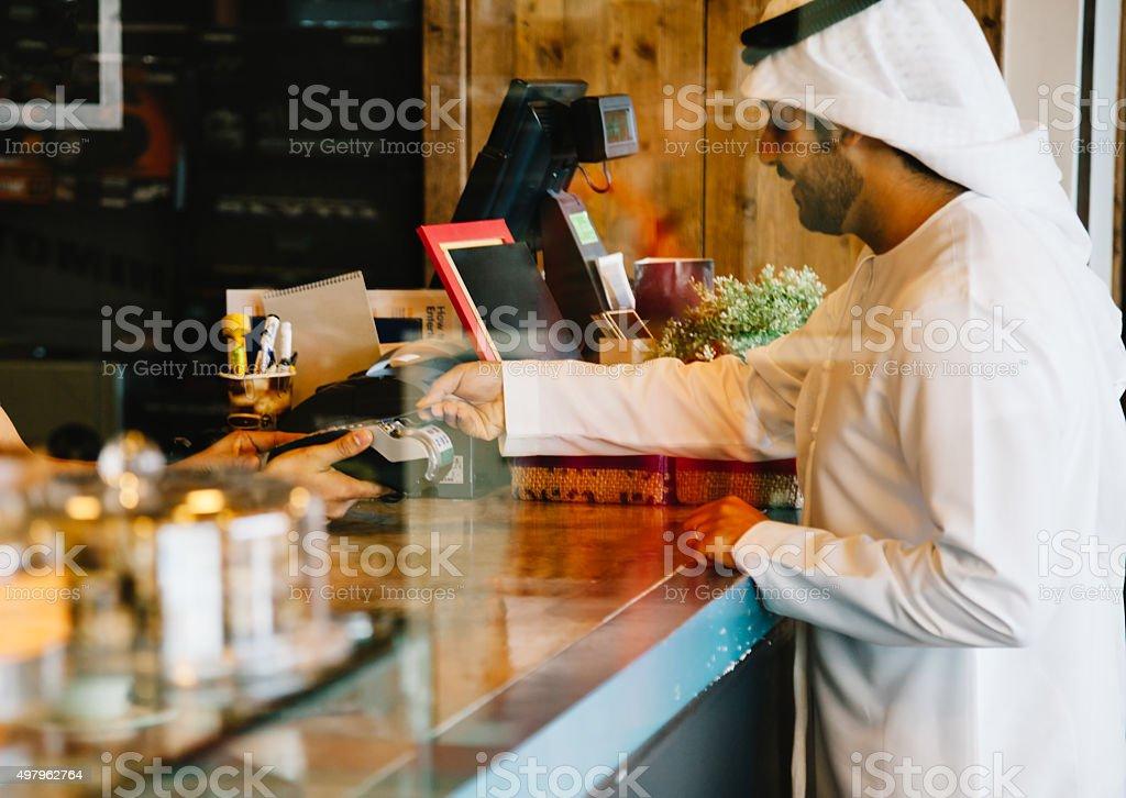 Emirati man paying via credit card at cafe stock photo