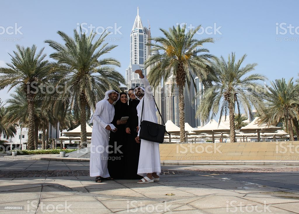Emirati men and woman taking a selfie, Dubai, UAE stock photo