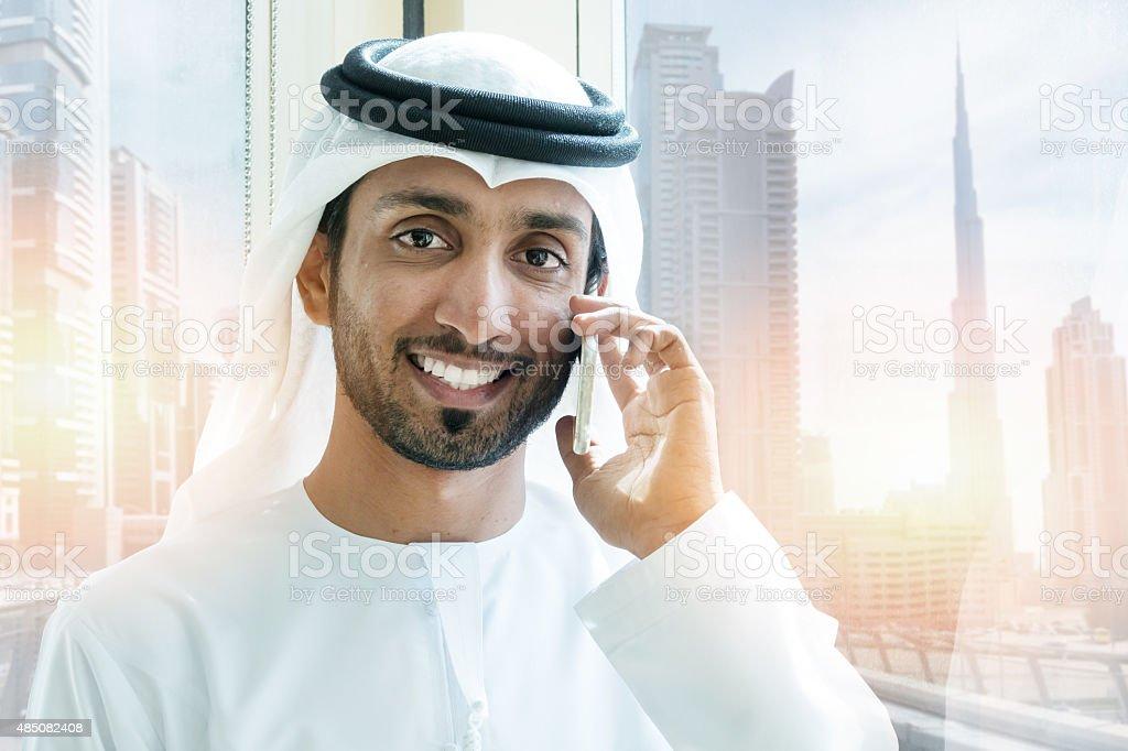 Emirati smiling businessmen in Dubai with mobile phone stock photo