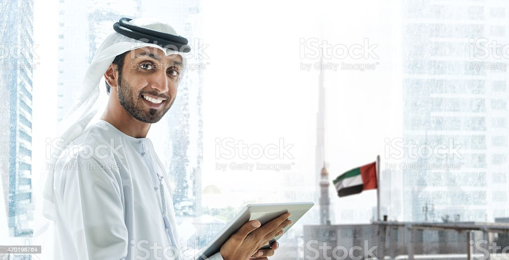 Emirati smiling businessmen in Dubai with tablet stock photo