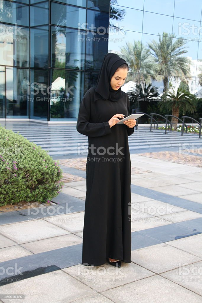 Emirati woman in traditional dress holding mobile device, Dubai, UAE stock photo
