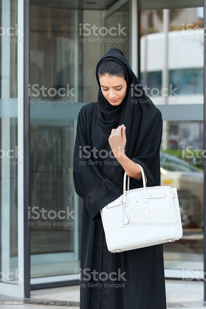 Emirati Woman Leaving Revolving Door Entrance and Looking in Handbag stock photo