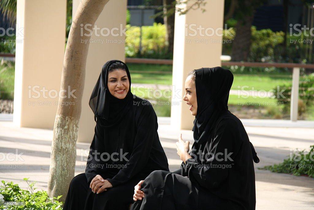 Emirati women talking in the park, Dubai, UAE stock photo