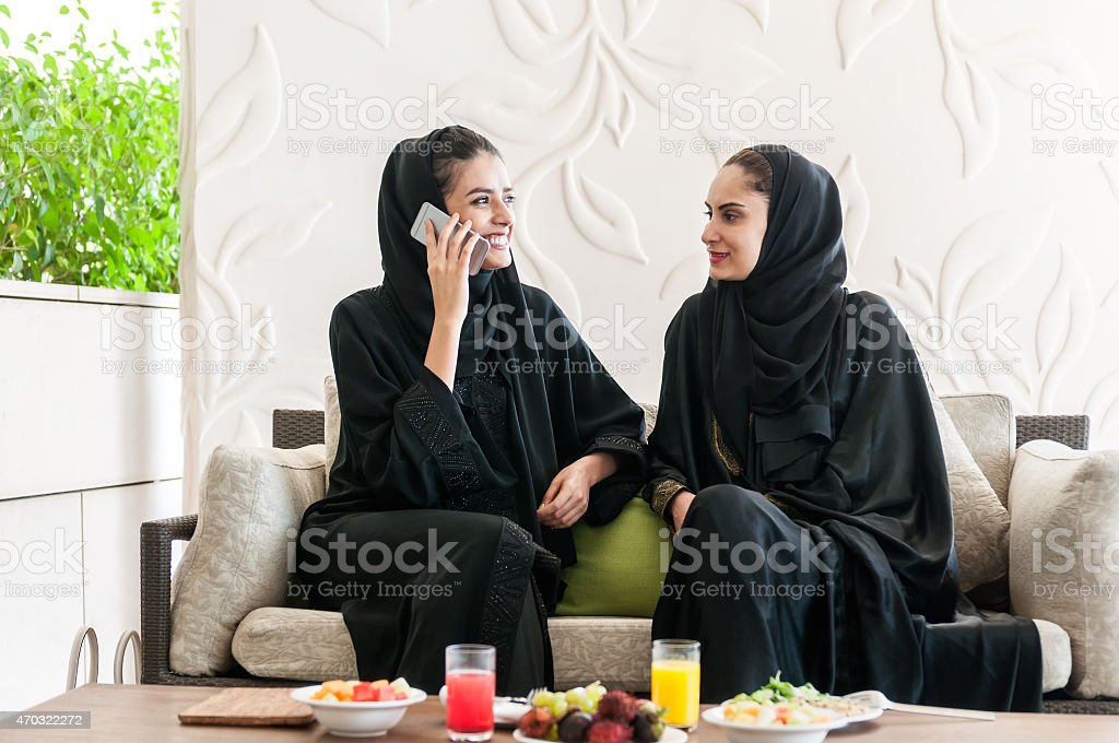 Emirati Women Wearing Abaya Eating Lunch and Talking on Cellphone stock photo