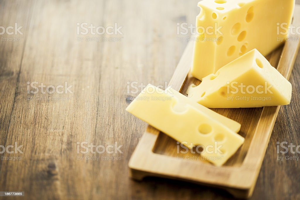 Emmental cheese placed on wooden board plate stock photo