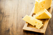 Emmental cheese placed on wooden board plate
