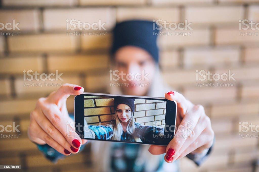 Emo girl taking selfie against brick wall stock photo