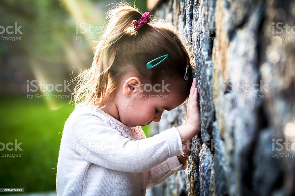emotion girl sitting near wall in the day time stock photo