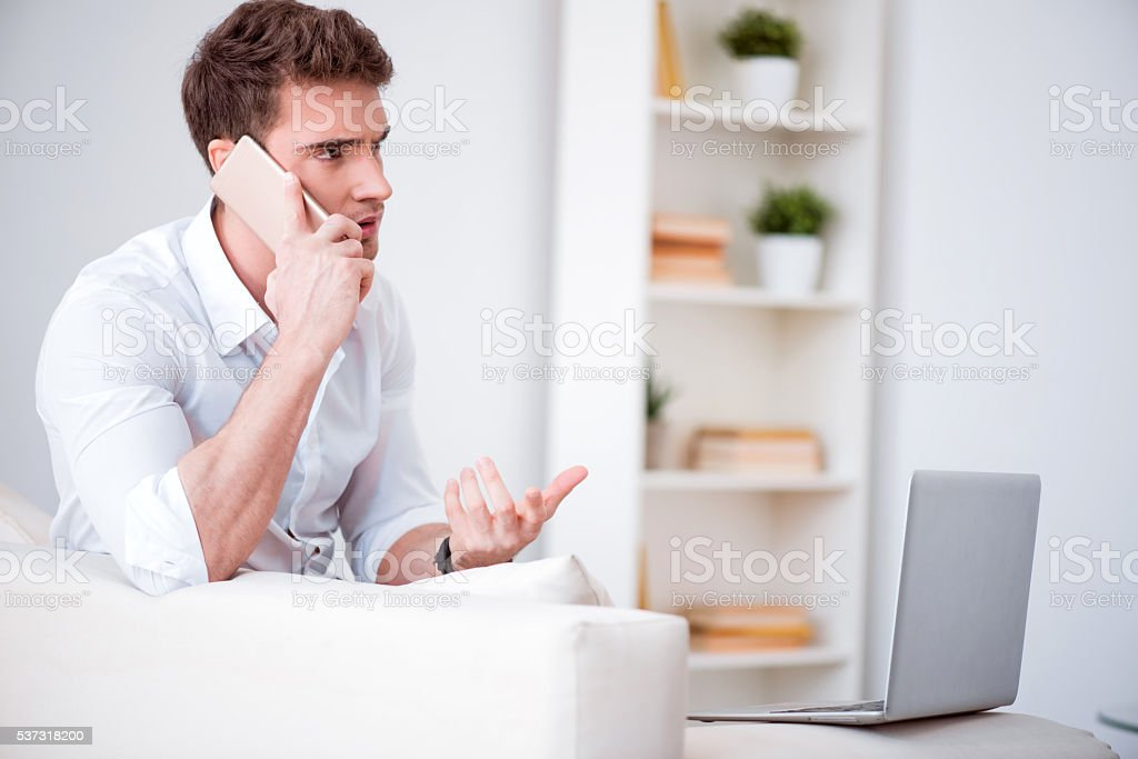 Emotional handsome man talking on cell phone stock photo