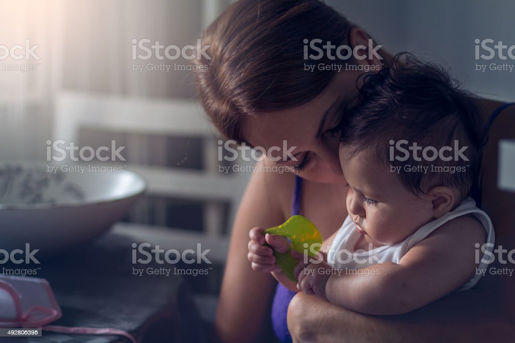 Emotional photo of a mother kissing her baby stock photo