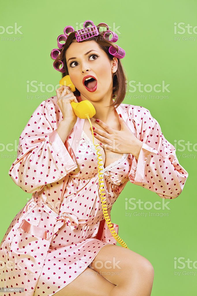 Emotional Pin-up Girl with curlers and phone stock photo