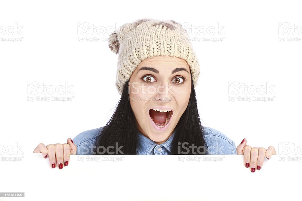 emotional teenage girl with a hat hiding behind billboard royalty-free stock photo