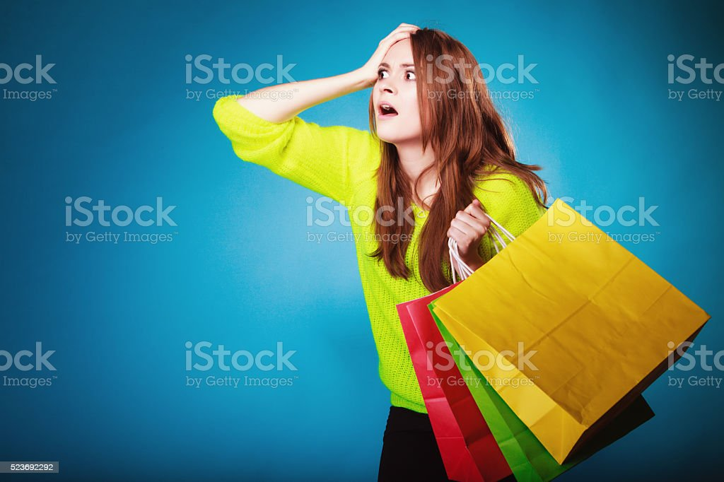 emotional woman with paper shopping bags on blue. stock photo