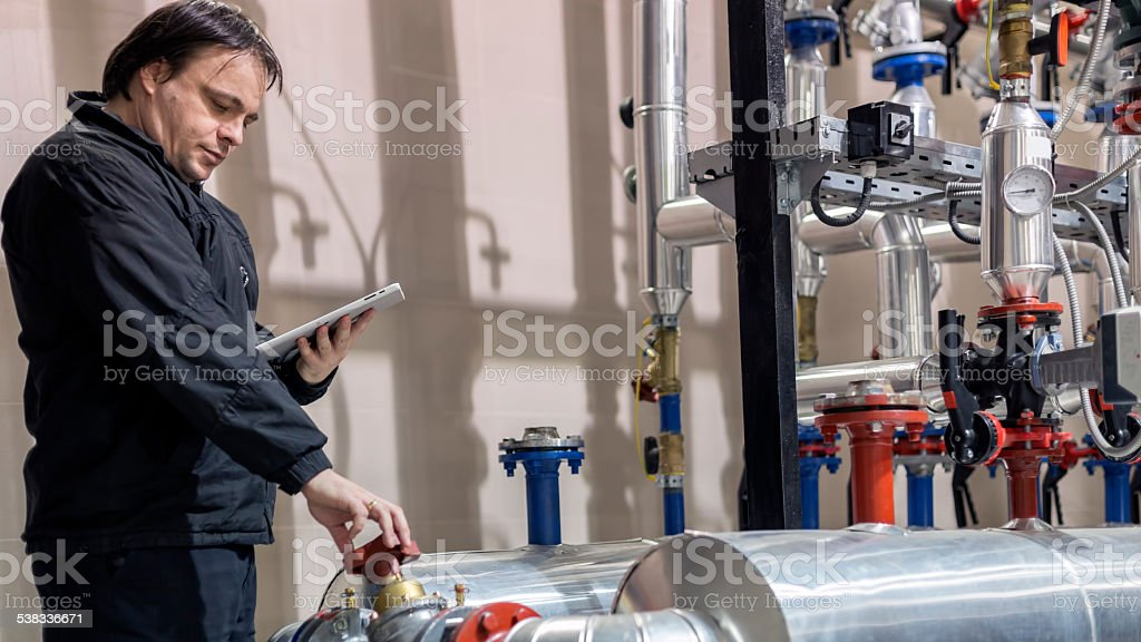 Employee checking valve in boiler room stock photo