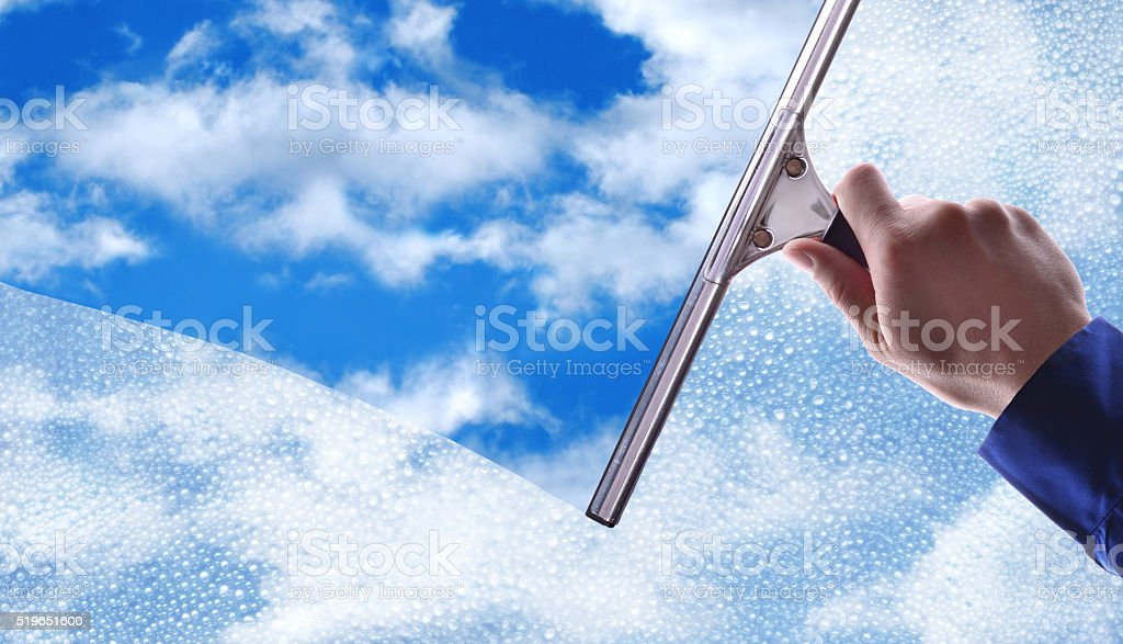 Employee cleaning a glass with rain drops and blue sky stock photo
