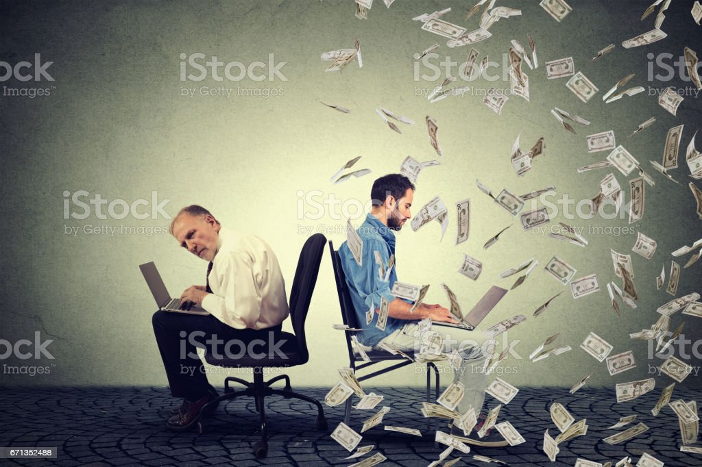 Employee compensation economy. Young and old man working on laptop stock photo