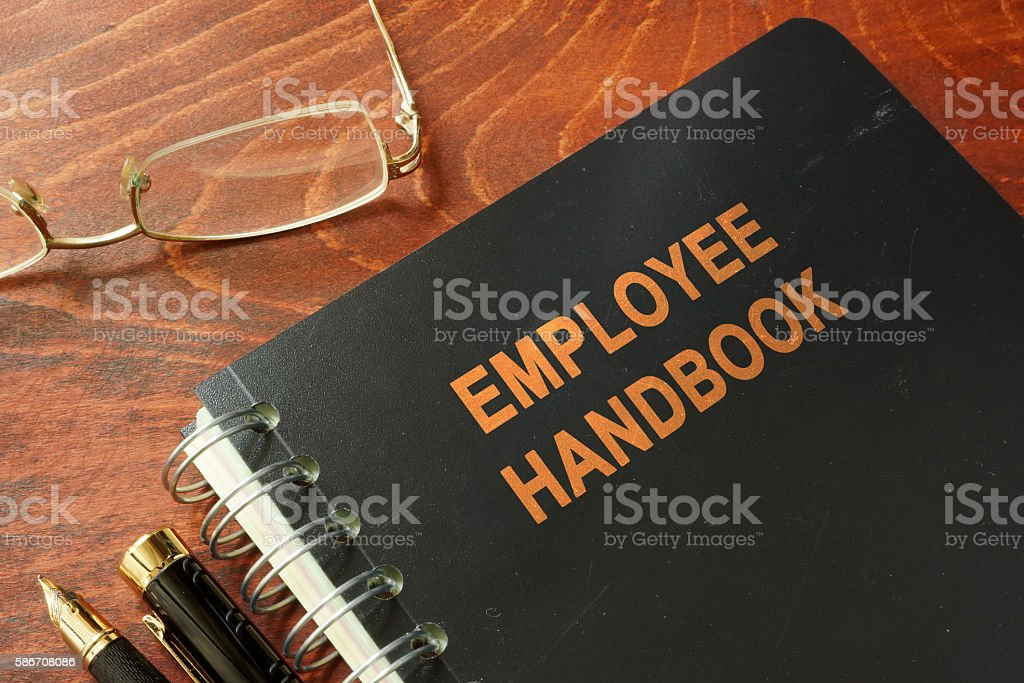 Employee handbook on a wooden table and glasses. stock photo